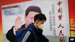 """北京街道上,戴口罩的行人走过带有中国领导人习近平像的海报,海报上有标语""""中国梦人民的梦""""(2017年10月26日)"""