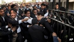 A lawyer (c) who spoke to the media supporting student leader Kanhaiya Kumar, is beaten up by other lawyers outside a Delhi court, in New Delhi, India, Feb. 17, 2016.