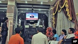 Yemenis watch a TV broadcasting an audio broadcast of Yemeni President Ali Abdullah Saleh, in a hotel in Taiz, Yemen, Friday, June 3, 2011