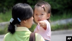 FILE - A North Korean defector carries a baby at the South Korean Hanawon resettlement facility in Anseong, 77 kilometers south of Seoul.