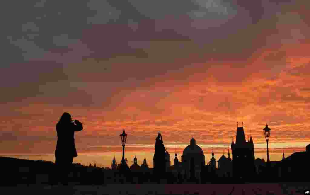 Woman takes a photograph of the medieval Charles Bridge as the sun rises in Prague, Czech Republic.