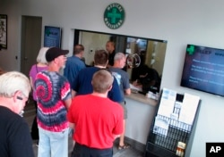 FILE - People line up to be among the first in Nevada to legally purchase medical marijuana at the Silver State Relief dispensary in Sparks, Nev. Nevada's marijuana regulators began recreational sales July 1, 2017.