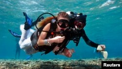 An assistant escorts a model as she dives to a location of an underwater photo shoot in the Red Sea in the resort city of Eilat, Oct. 23, 2013.