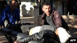 Dalam foto yang dirilis Kantor Berita Kurdi Suriah Utara, tampak seorang pria yang cedera dibawa ke rumah sakit di Kota Tal Rifaat setelah serangan artileri Turki yang menarget kawasan dekat sebuah sekolah, 2 Desember 2019. (Foto: AFP)