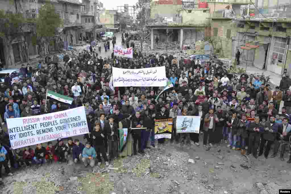 Demonstrators hold banners near damaged buildings during a protest against Syria's President Bashar al-Assad, after Friday prayers in Kafranbel near Idlib December 14, 2012. REUTERS/Raed Al-Fares/Shaam News Network/Handout (SYRIA - Tags: CIVIL UNREST MILI