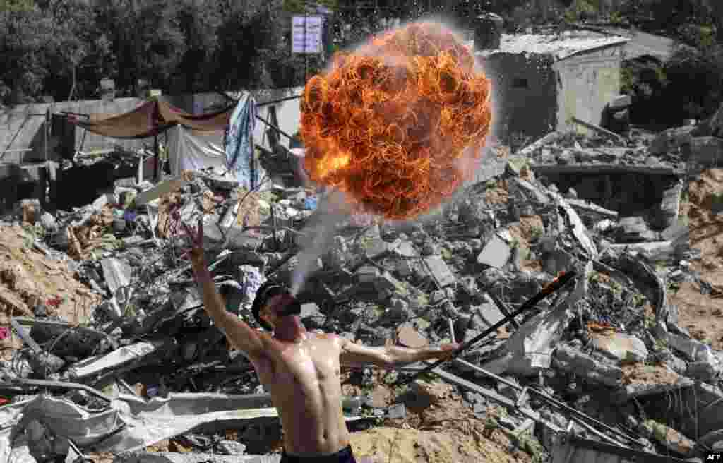 Palestinian members of Gaza's Bar Woolf sports team perform with fire on the ruins of a building destroyed in recent Israeli airstrikes, in Beit Lahia.