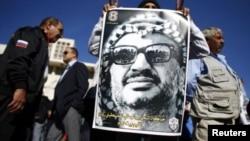 在約旦河西岸的一次集會中一名男子舉著印有阿拉法特頭像的海報。