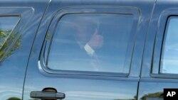 Donald Trump saluda desde su camioneta al salir de la reunión con los legisladores republicanos.
