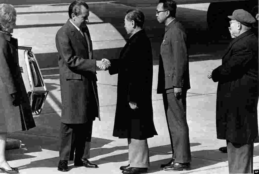 """1972年2月21日中国总理周恩来在北京机场欢迎美国总统尼克松。 尼克松曾经将他1972年对中国的访问形容为""""改变世界的一星期"""" 。周恩来身后站着翻译冀朝铸。但当时中方发表的照片却被修图,冀朝铸变成空白,而翻译王海容被放到前面。后来有中国报刊报道说:""""冀朝铸并没有详细解释个中原委,这个小插曲似乎也是那个时期国内复杂政治斗争的微妙体现吧。""""冀朝铸是从美国回中国的哈佛学生,是周恩来的亲信,后来当过联合国副秘书长,卸任后有批毛言论。而王海容是毛泽东的表侄孙女,文革期间曾任副外长,与毛关系密切。 毛死后,其亲信文革派政要被捕,王海容也曾被停职审查。"""