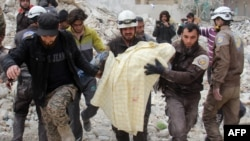 FILE - Members of the Syrian civil defense, known as the White Helmets, remove a victim from the rubble of a destroyed building following a reported airstrike in the northwestern city of Idlib, March 15, 2017.