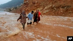 Men walk on a road flooded after heavy rain and strong winds caused damage in Hadibu as Cyclone Mekunu pounded the Yemeni island of Socotra, May 24, 2018. At least 17 people were reported missing and presumed dead. The powerful storm remained on path to strike Oman this weekend.