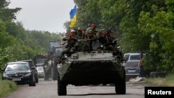 Ukrainian soldiers ride atop an Armored Personnel Carrier (APC) near the site where pro-Russia rebels killed Ukrainian servicemen in the outskirts of the eastern Ukrainian town of Volnovakha, south of Donetsk May 22, 2014.
