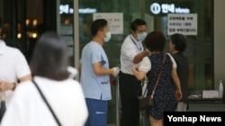 지난 7월 한국 일원동 삼성서울병원에서 관계자들이 방문객들을 대상으로 발열검사를 하고 있다. (자료사진)
