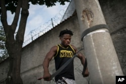 In this May 27, 2016 photo, Popole Misenga, a refugee and judo athlete from the Democratic Republic of Congo, uses a judo black belt attached to a street light pole to trains near his home in Rio de Janeiro, Brazil.