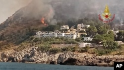 Woodland fires burn near a tourist resort where, according to firefighter reports, some several hundred tourists have been evacuated by land and sea, in the Sicilian town of San Vito lo Capo, southern Italy, July 12, 2017.