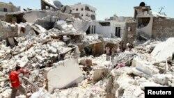 Cư dân đứng trên đống đổ nát của nhà cửa của họ sau các vụ không kích của lực lượng chính phủ vào Bab Neirab, Aleppo.