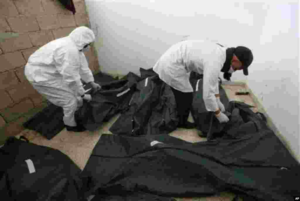 Libyan mortuary assistants look to unidentified dead burned bodies who were killed last week during the demonstration against country's leader Moammar Gadhafi at a morgue hospital, in Benghazi, February 24, 2011. (AP Image)