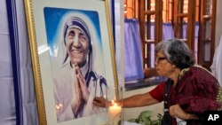 An Indian Catholic woman offers prayers as she touches a portrait of Mother Teresa on her 17th death anniversary at the Missionaries of Charity in Kolkata, India, Sept. 5, 2014.
