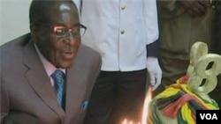 Presiden Zimbabwe Robert Mugabe meniup lilin saat merayakan Ulang Tahun ke-88 (21/2).
