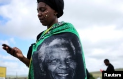 A woman, draped in a cloth with an image of former South African President Nelson Mandela, uses a mobile phone during Mandela's funeral at his ancestral village of Qunu in Eastern Cape province, south of Johannesburg, Dec. 15, 2013.