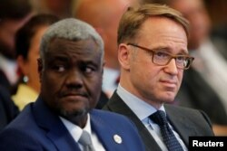 FILE - Moussa Faki Mahamat, African Union Commission Chairperson, left, attends a Summit in Berlin, Germany, June 13, 2017.
