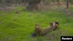 Seorang tentara sukarela Israel melewatkan waktunya dengan bersantai di padang rumput dekat perbatasan Israel di sebelah utara Gaza pasca diumumkannya gencatan senjata (22/11). Israel telah melonggarkan sejumlah pembatasan di wilayah perbatasan pasca gencatan senjata.