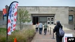 Les gens entrent dans un auditorium de la Morgan State University pour voter, le deuxième jour du vote anticipé de la course présidentielle américaine, à Baltimore, le 27 octobre 2020.
