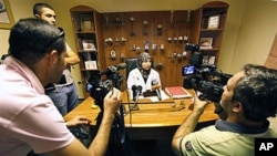 Lebanese Dr. Iman Sharara, center, tells journalists that dozens of women stormed her clinic as international investigators were visiting her, south of Beirut, Lebanon, 27 Oct 2010