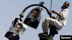 Một thành viên nhóm Huynh đệ Hồi giáo ủng hộ tổng thống bị lật đổ Mahamed Morsi treo ảnh ông lên một cột đèn trong một cuộc biểu tình trước tòa án ở Cairo, 22/7/13