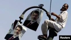 2013年7月22日在埃及首都开罗的司法部外面的抗议示威中,被推翻的总统穆尔西的支持者在路灯上高挂穆尔西的照片。