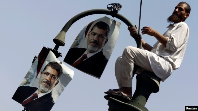 A member of the Muslim Brotherhood and supporter of ousted Egyptian President Mohamed Morsi places posters of Morsi on a lamp post, during a protest in front of the courthouse and the Attorney General's office, in Cairo, July 22, 2013.