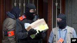 Belgium police leave after an investigation in a house in the Anderlecht neighborhood in Brussels, Belgium, March 23, 2016.