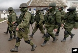 FILE - Troops, believed to be Russian special forces in uniforms without insignia, march outside a Ukrainian military base in Perevalne, Crimea, March 20, 2014.