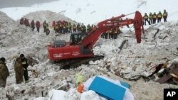 This picture made available Jan. 24, 2017 by the Italian Mountain Rescue Service 'Corpo Nazionale Soccorso Alpino e Speleologico' shows an excavator at the site of the avalanche-buried Hotel Rigopiano, near Farindola. Italy.