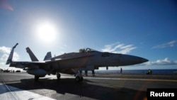FILE - A F/A 18E Super Hornet on the deck of the aircraft carrier USS Ronald Reagan, July 6, 2010.