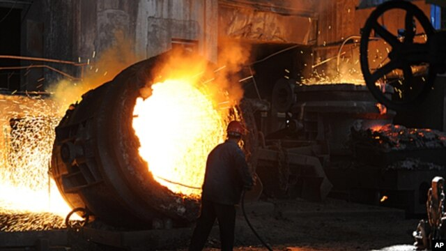 A worker stokes a giant burning cauldron at a steel mill in Hefei, in eastern China's Anhui province, June 25, 2011 (file photo)