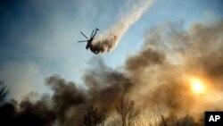美國西部加利福尼亞州的消防隊員在控制山林大火。直升機正投放水以滅火。