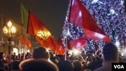 Partai Komunis Rusia melambaikan bendera partainya dalam aksi protes terkait hasil pemilu Rusia di Moskow (5/12).