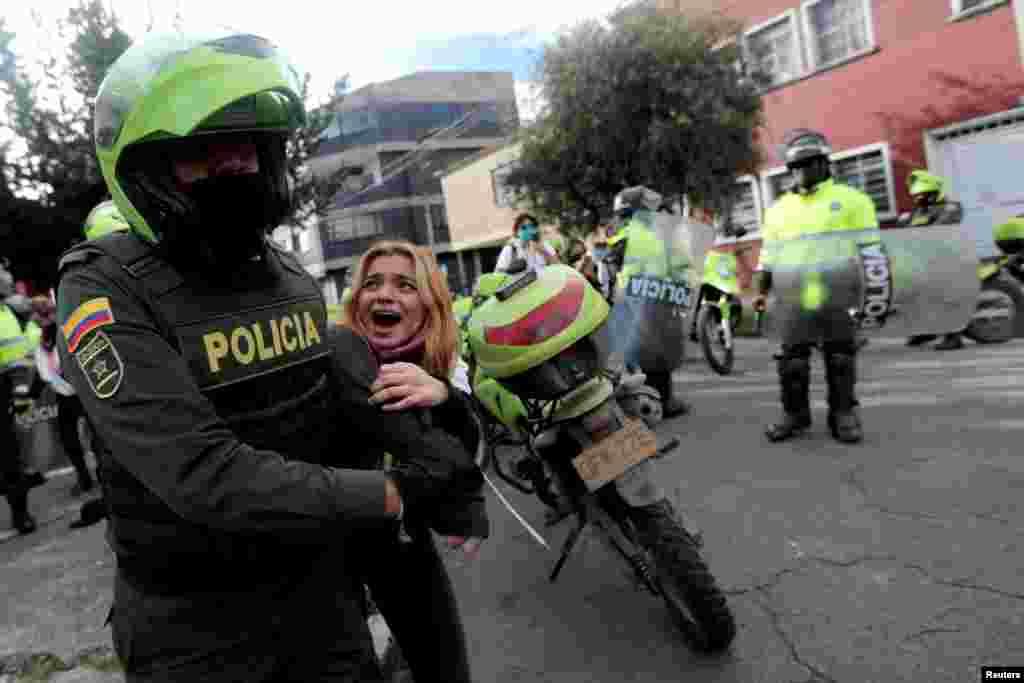បាតុករម្នាក់ត្រូវបានប៉ូលិសចាប់ខ្លួននៅក្នុងបាតុកម្មមួយទាមទារឲ្យមានជីវិតថ្លៃថ្នូរ អំឡុងពេលមានជំងឺរាតត្បាតក្នុងទីក្រុង Bogota ប្រទេសកូឡុំប៊ីកាលពីថ្ងៃទី១៥ ខែមិថុនា ឆ្នាំ២០២០។