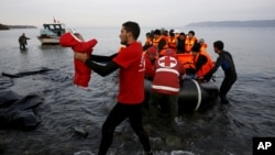 A Red Cross volunteer carries a Syrian refugee baby off an overcrowded raft at a beach on the Greek island of Lesbos, Nov. 16, 2015. Some Republicans are pushing back against aggressive opposition in their party to Syrian refugees resettling in the U.S.