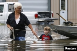 FILE - Richard Rossi and his 4-year-old great grandson, Justice, wade through water in search of higher ground after their home took in water in St. Amant, Louisiana, Aug. 15, 2016