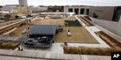 Work crews rush to set up a stage beside the state's two newest museums, the Museum of Mississippi History and the Mississippi Civil Rights Museum, Dec. 7, 2017, in Jackson, Mississippi.