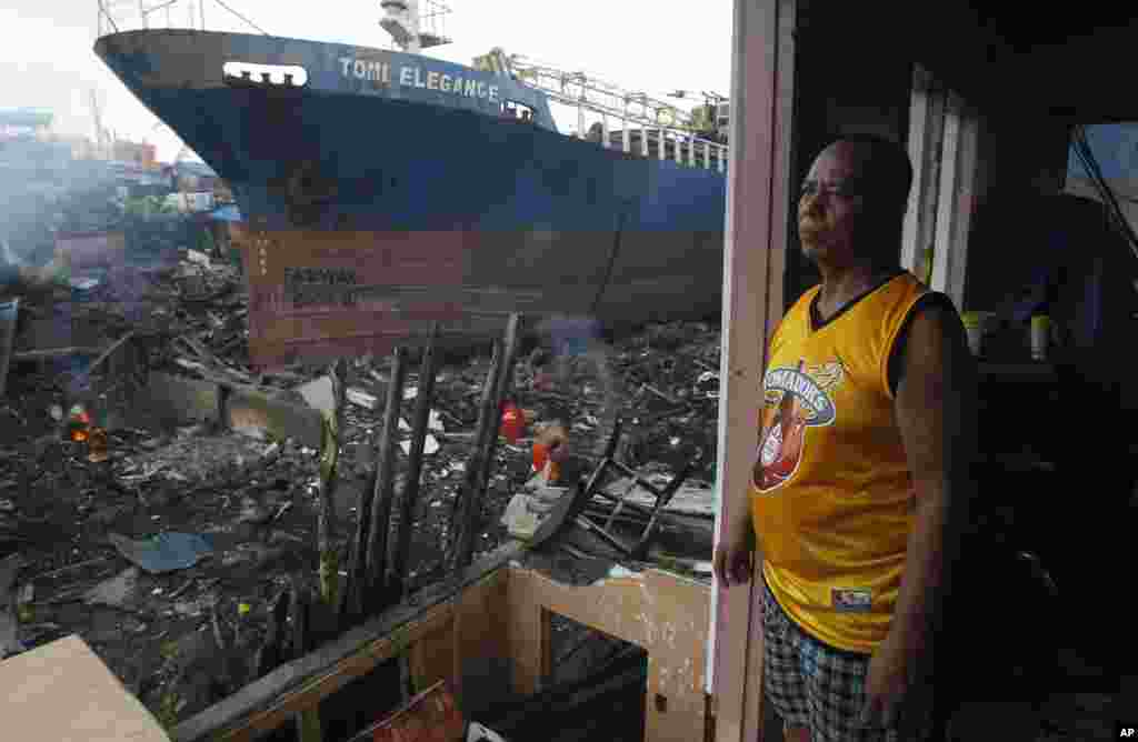 Typhoon survivor Manolito Pacurib stands inside his damaged home near a shipping vessel that remains grounded after being washed ashore during Typhoon Haiyan, in Tacloban, Philippines, Dec. 23, 2013.