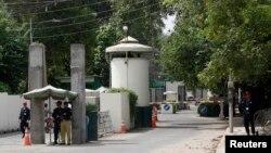 Seorang polisi (dua dari kanan) dan petugas keamanan berjaga di pintu gerbang menuju kantor Konsulat AS di Lahore (9/8).