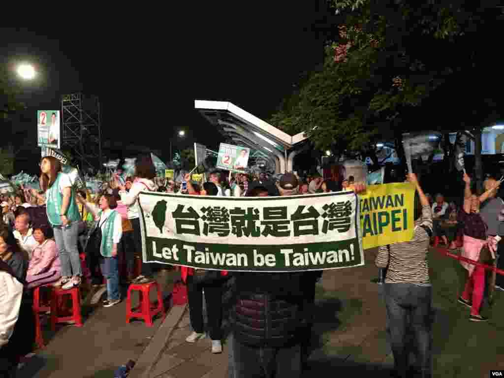 民進黨籍台北市長候選人姚文智11月21日的造勢晚會上,一名支持者打出橫額。 (美國之音許寧拍攝)