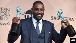 "Idris Elba poses in the press room with the award for outstanding male actor in a supporting role for ""Beasts of No Nation"" and the award for outstanding male actor in a TV movie or miniseries for ""Luther"" at the 22nd annual Screen Actors Guild Awards at"