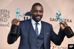 "Idris Elba poses in the press room with the award for outstanding male actor in a supporting role for ""Beasts of No Nation"" and the award for outstanding male actor in a TV movie or miniseries for ""Luther"" at the 22nd annual Screen Actors Guild Awards in Los Angeles, Jan. 30, 2016."