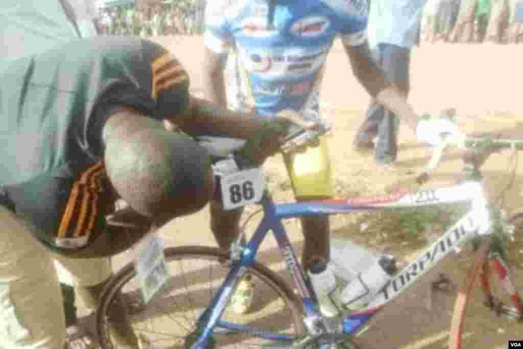Un cycliste malien essaie de regler son vélo lors de la 5e étape entre Pa et Bobo-Dioulasso, 3 nov. 2015. Photo Salif kaboré.