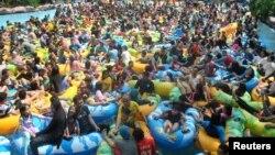Para pengunjung memadati kolam renang saat liburan Idul Fitri, di Bogor, Jawa Barat, 18 Juni 2018. (Foto: Antara via Reuters)