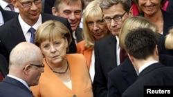 La canciller alemana Angela Merkel y sus colegas parlamentarios se alinean para votar por un paquete de ayuda a Europa. La presión sobre la canciller para que deje ir a Grecia va en aumento.